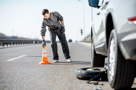Road assistance worker putting emergency cones near the broken car on the highway Reklamní fotografie - 120346326