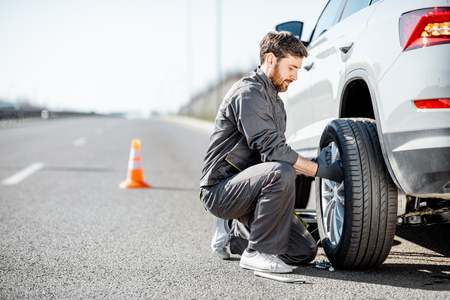 Handsome road assistance worker in uniform changing car wheel on the highway Standard-Bild