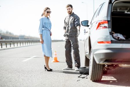 Trabajador de asistencia vial en uniforme con mujer joven de pie cerca del coche roto en la carretera