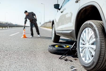 Trabajador de asistencia vial poniendo conos de emergencia cerca del coche roto en la carretera