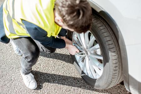 Man in vest unscrewing the broken wheel on the roadside