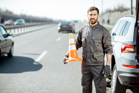 Portrait of a happy road assistance worker in uniform standing with cone near the car on the roadside Stok Fotoğraf