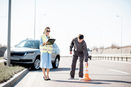 Woman and road assistance worker during the road accident on the highway Stock Photo
