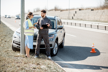 Woman with road assistance worker signing some documents standing near the car in road accident on the highway Banque d'images