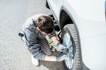 Worker unscrewing car wheel on the road, view from above Stockfoto