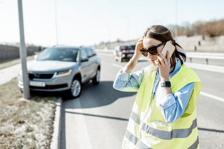 Embarrassed woman calling road assistance standing near the car during the road accident on the highway