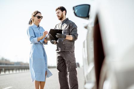 Trabajador de asistencia vial firmando algunos documentos con una mujer cerca del coche roto en la carretera