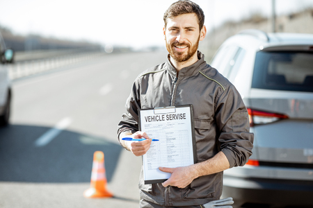 Portrait of a road assistance worker stnading with vehicle service document near the car on the highway Stok Fotoğraf