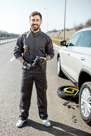 Portrait of a handsome road assistance worker in uniform standing near the broken car on the highway