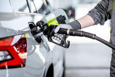 Trabajador de la gasolinera repostar el coche con gasolina, vista cercana se centró en la pistola de llenado