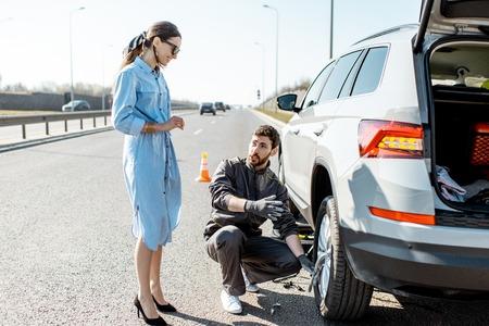 Operatore dell'assistenza stradale che aiuta una giovane donna a cambiare la ruota di un'auto in autostrada