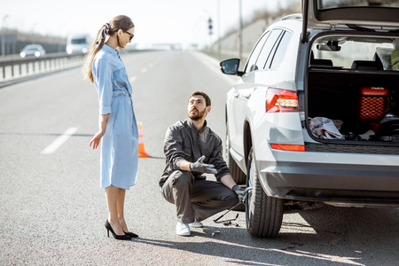 Road assistance worker helping young woman to change a car wheel on the highway Stok Fotoğraf