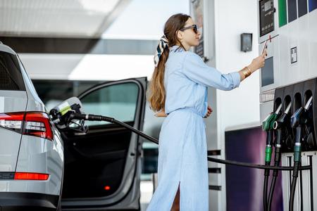 Mujer pagando con teléfono por gasolina, fotografiando código de barras en la bomba de la gasolinera Foto de archivo