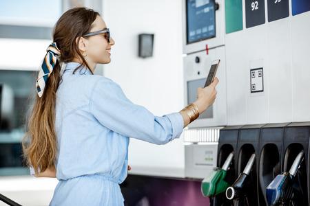 ガソリンのために電話で支払う女性、ガソリンスタンドのポンプでバーコードを撮影