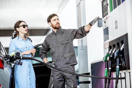 ガソリンスタンドで車に給油ガソリンスタンド労働者と若い女性クライアント