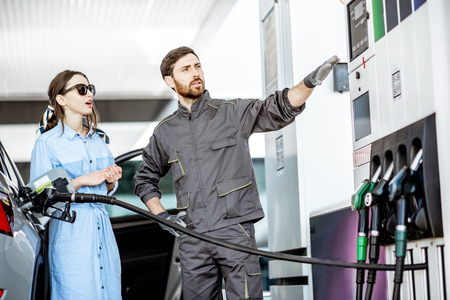 Young woman client with gas station worker refueling car at the gas station