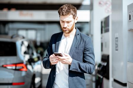 Biznesmen z inteligentnym telefonem podczas tankowania samochodu na stacji benzynowej
