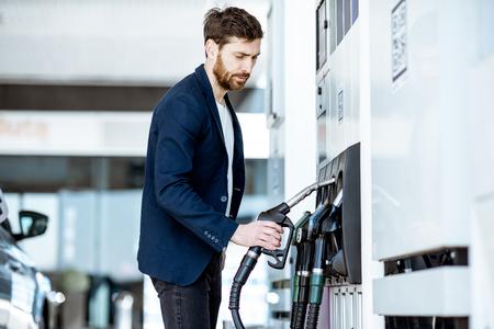 Businessman refueling his luxury car holding filling gun at the gas station Reklamní fotografie