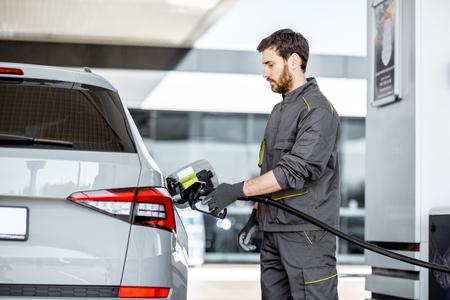 ガソリンスタンドでガソリンを持つ高級車に給油する作業服のガソリンスタンド労働者は、駅で銃を充填します