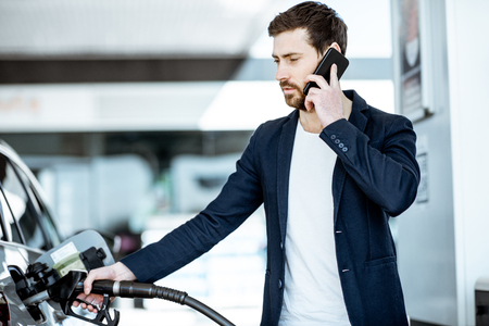 Businessman talking with phone while refueling car at the gas station
