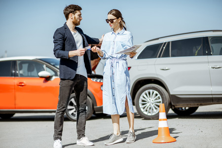 Man and woman arguing, standing together on the road with their cars on the background after the car accident