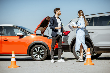 Man and woman arguing, standing together on the road with their cars on the background after the car accident Zdjęcie Seryjne