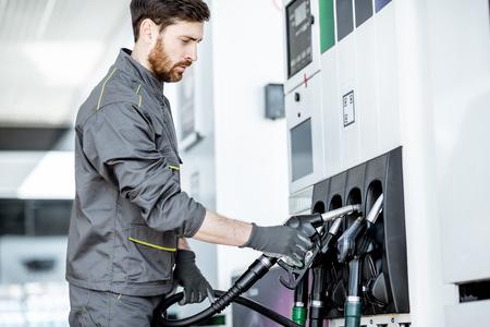 Pracownik stacji benzynowej w mundurze biorący pistolet do napełniania, tankowanie samochodu na stacji benzynowej