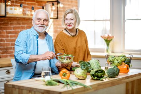 Pareja senior alegre comiendo ensalada de pie junto con comida sana en la cocina de casa. Concepto de nutrición saludable en la vejez