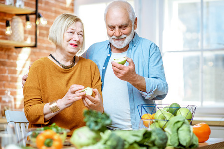 Porträt eines fröhlichen Seniorenpaares, das Äpfel isst, die zusammen mit gesundem Essen in der Küche zu Hause stehen Standard-Bild