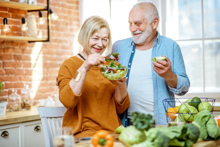 Ritratto di una coppia senior allegra con insalata e cibo sano in cucina a casa. Concetto di alimentazione sana in età avanzata