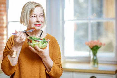 Beautiful senior woman eating fresh salad at home. Concept of healthy nutrition in older age