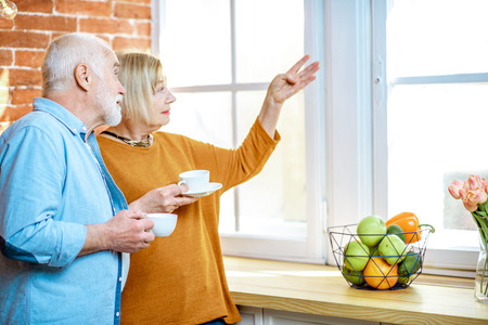 Portrait of a lovely senior couple standing together with coffee cups, looking out the window at home Stock Photo