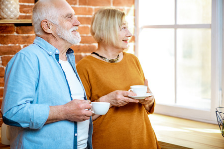 Portrait of a lovely senior couple standing together with coffee cups, looking out the window at home Stok Fotoğraf