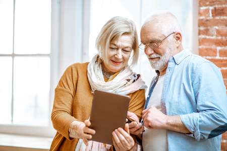 Beautiful senior couple using digital tablet standing together near the window at home
