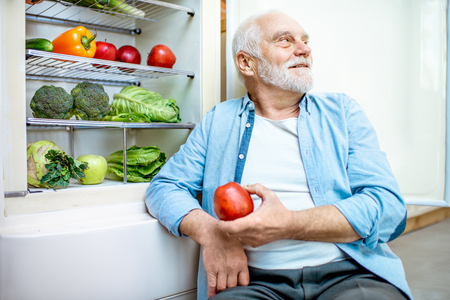 Portrait of a thoughtful senior man sitting with apple near the refrigerator full of healthy food at home 写真素材