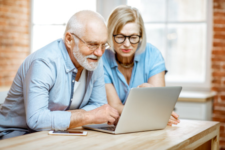 Portrait of a beautiful senior couple in blue shirts feeling happy, sitting together with laptop at home