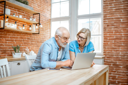 Beautiful senior couple in blue shirts sitting together with laptop on the kitchen at home 写真素材