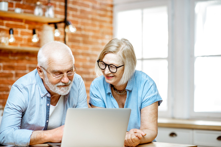 Beautiful senior couple in blue shirts feeling happy, sitting together with laptop on the kitchen at home