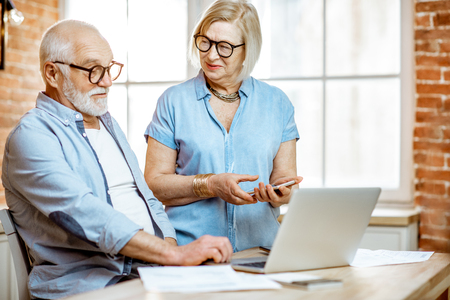 Beautiful senior couple in blue shirts working together with laptop on the kitchen at home