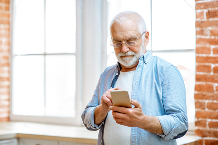 Cheerful senior grandfather using phone standing near the window at home
