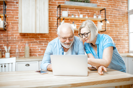 Beautiful senior couple in blue shirts sitting together with laptop on the kitchen at home Imagens