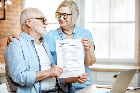 Portrait of a happy senior couple holding resume document indoors. Concept of work in older age 写真素材 - 121137820