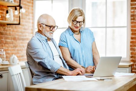 Beau couple de personnes âgées en chemises bleues travaillant avec un ordinateur portable dans la cuisine à la maison Banque d'images