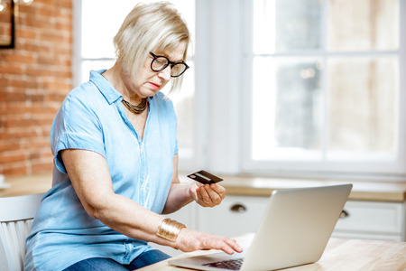 Modern senior woman shopping online using credit card and laptop at home Stock Photo
