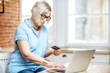 Modern senior woman shopping online using credit card and laptop at home Reklamní fotografie