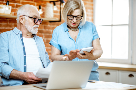 Senior couple with embarrassed emotions calculating some bills or taxes sitting with laptop on the kitchen at home 写真素材