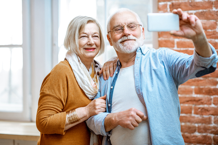 Happy senior couple making selfie photo or talking online using smart phone at home