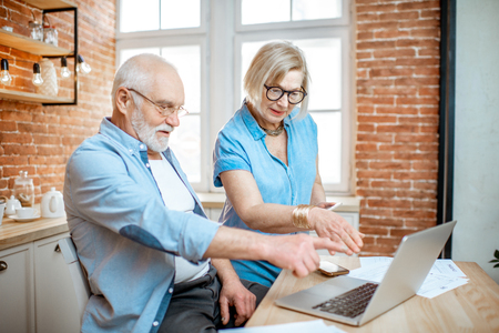 Beautiful senior couple in blue shirts sitting together with laptop on the kitchen at home Stock fotó