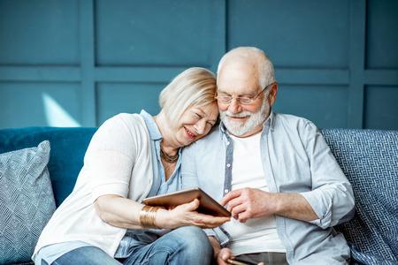 Encantadora pareja senior vestida informalmente con tableta digital mientras está sentado juntos en el cómodo sofá en casa