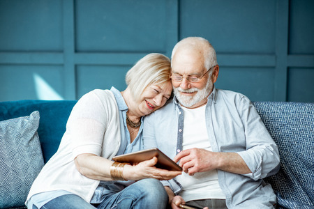 Urocza para starszych ubrana swobodnie, korzystająca z cyfrowego tabletu, siedząc razem na wygodnej kanapie w domu
